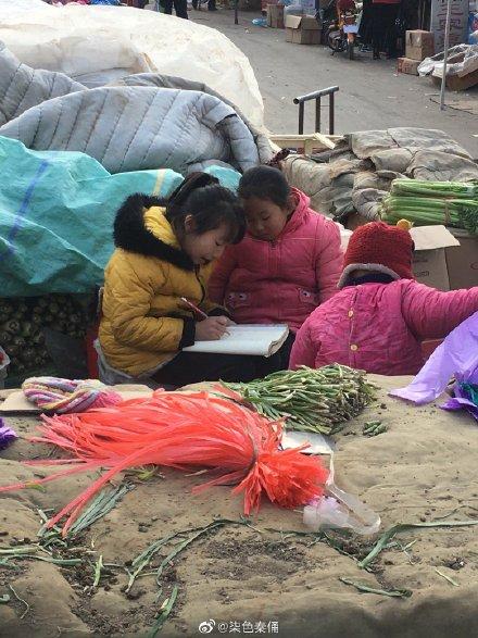 菜市場寫作業的女童。(網絡圖片)