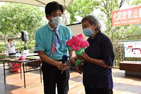 西嶺國小校長凃仁雄﹙左﹚致贈氣球造型康乃馨給高齡94歲的藍女士﹙右﹚。