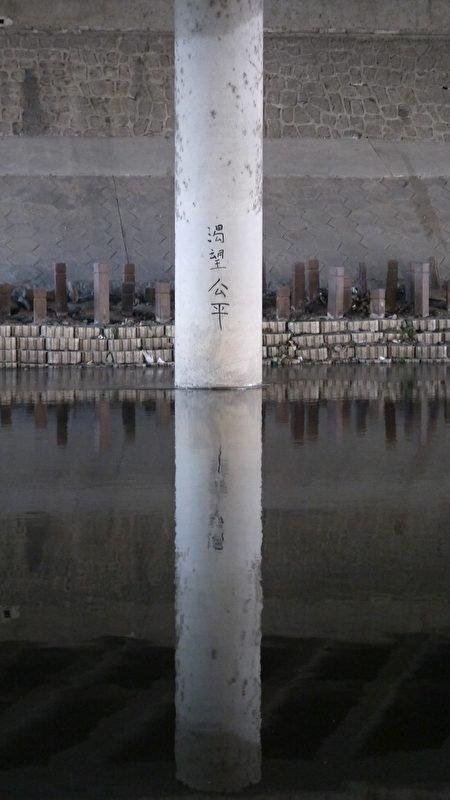2016年,北京南站涼水河下,訪民寫的標語口號,後面是政府為防止訪民露宿,在土地上釘上了樁子。(大紀元)