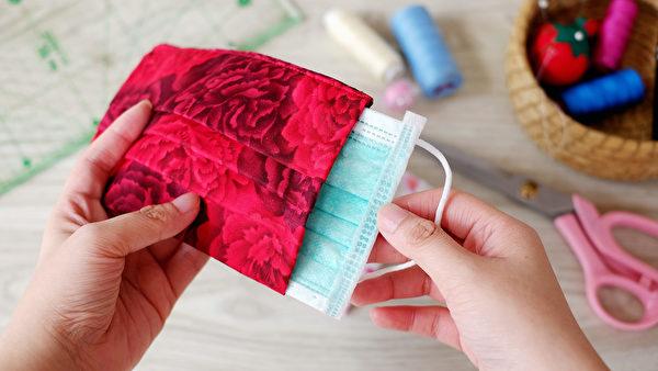 自製「布口罩套」增加防護病毒的功能,在兩片布中間置入一片「不織布材質」,示意圖放入外科口罩。(shutterstock)