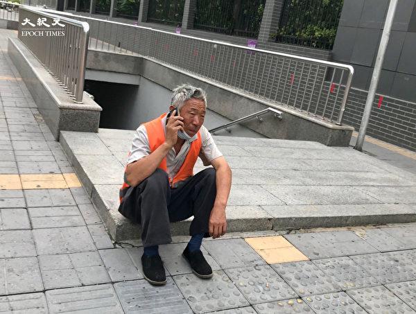 2020年6月25日,北京站一位環衛工人給兒子打電話:「你吃粽子了沒?我在這邊可好了,想吃啥吃啥。」(大紀元)