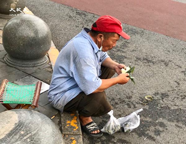 2020年6月25日,北京街頭,吃粽子的民工。(大紀元)