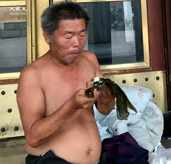 2020年6月25日,北京街頭,吃粽子。(大紀元)