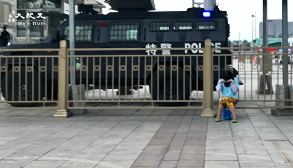 2020年6月25日,一女子在北京站特警車前哭泣。(大紀元)
