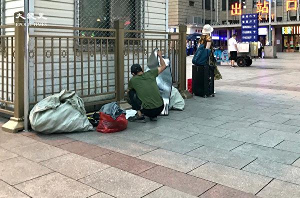 2020年6月25日,一男子在北京站的出站口崗亭外鋪上床鋪準備過夜。(大紀元)