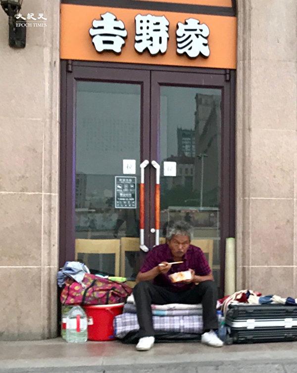 2020年6月25日,北京站的吉野家已經關閉,有人在門口吃飯。(大紀元)