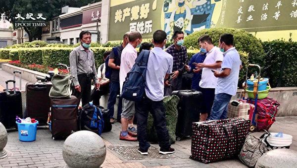2020年6月25日,準備返家但不能進北京站的農民工在商量怎麼辦。(大紀元)