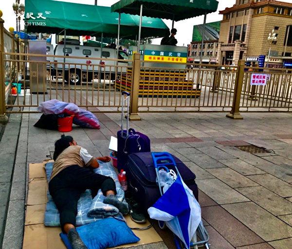 2020年6月25日,北京街頭,睡在武警車前的人。(大紀元)