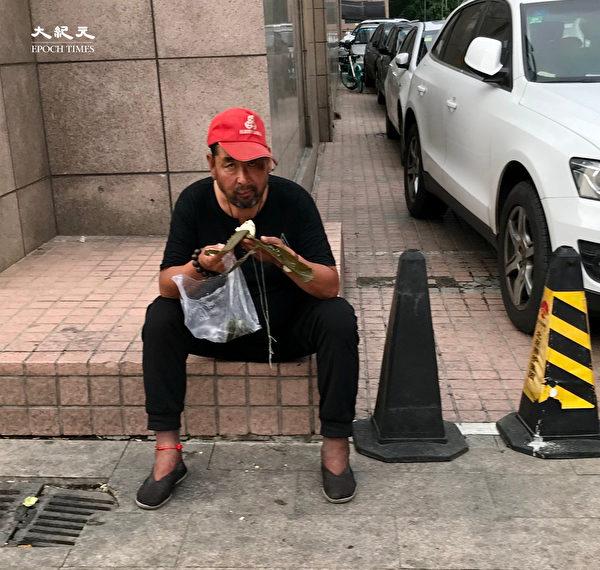 2020年6月25日,北京站,吃粽子的民工。(大紀元)