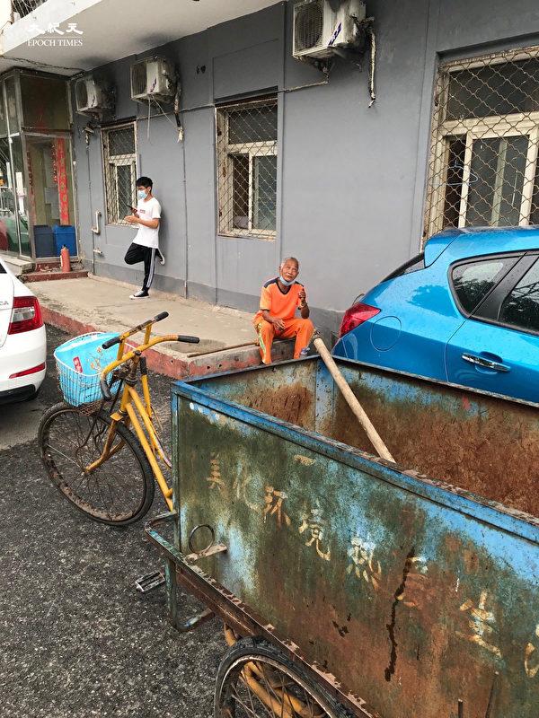 2020年6月25日,下雨了,北京站,避雨的保潔與男孩。(大紀元)