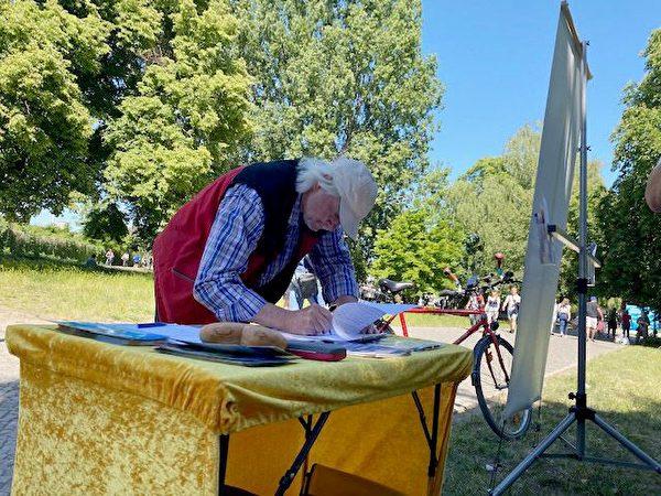 「聲援受迫害族群協會」成員烏利希在徵簽簿上簽字,反對中共迫害法輪功學員。(明慧網)