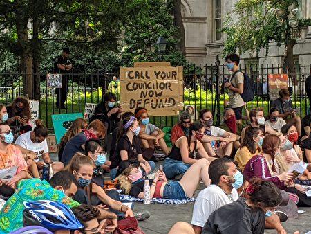 示威者在圍欄上掛著「Call your Councilor now Defund」標語。