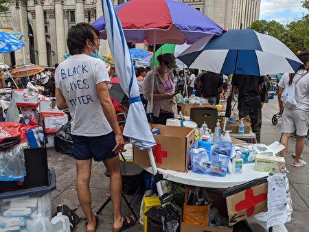 示威現場堆滿了各方捐贈的物資,包括洗手液和口罩等。