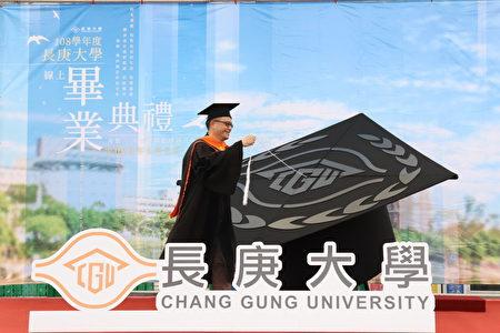 長庚大學在舞台上設置大型學士帽,圖為工商管理學系陳威志助理教授象徵性為畢業生進行撥穗禮。