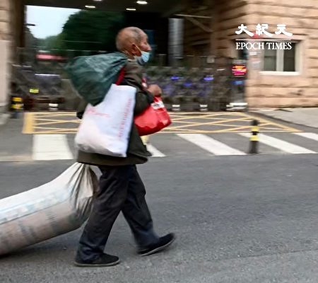 2020年6月27日,北京不能返家的民工,拖著自己的被褥在街上。(大紀元)