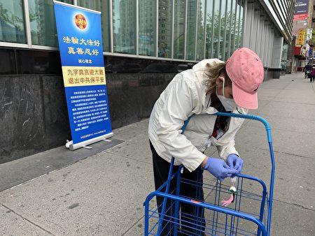 西人民眾接過「法輪大法好」的小蓮花,小心地把它繫在自己的推車上。(林丹/大紀元)