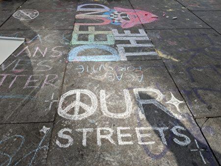 有示威抗議者在地上畫了反戰圖示,和醜化警察的圖像標語。