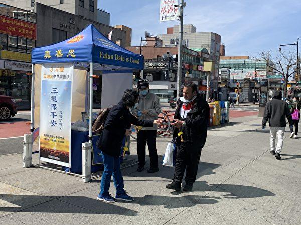 紐約疫情最高峰的4月初,法拉盛街頭的法輪功真相點照常開放,圖為民眾接過「法輪大法好」小蓮花和護身符。(林丹/大紀元)