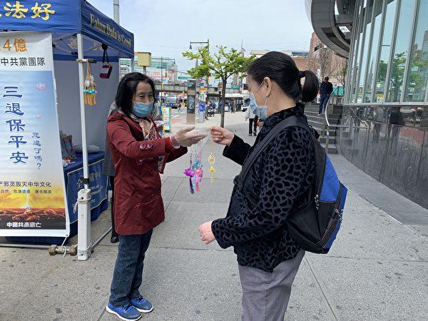 一位華人女子路過紐約法拉盛圖書館前的真相點,接過法輪功學員派發的「法輪大法好」小蓮花,後來她的同伴把小蓮花搶走扔掉,她默默地從地上撿起,重新放入口袋。(林丹/大紀元)