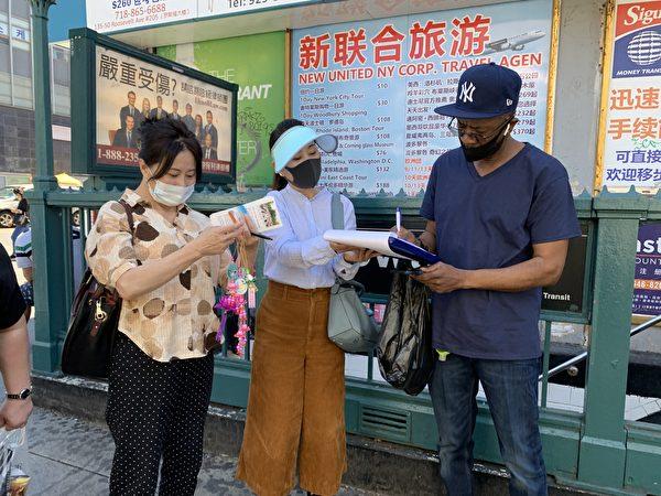 圖為一名非洲裔在「拒絕中共」(Reject the CCP)的倡議書上簽字。(林丹/大紀元)