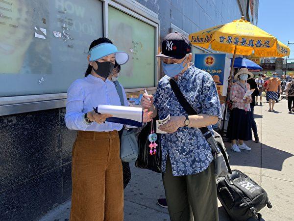 圖為一名亞裔民眾在「拒絕中共」倡議書上簽字。(林丹/大紀元)
