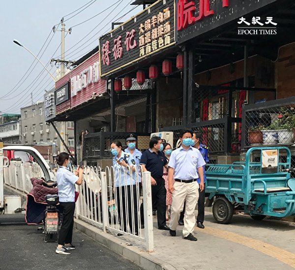 2020年6月27日,北京海淀區永定河路監管人員去店舖巡查。一上午能來四波不同的機構檢查,商家嘆如何做生意?(大紀元)