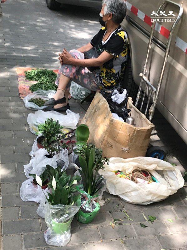 2020年6月27日,北京一位老年婦女躲著城管擺攤。(大紀元)