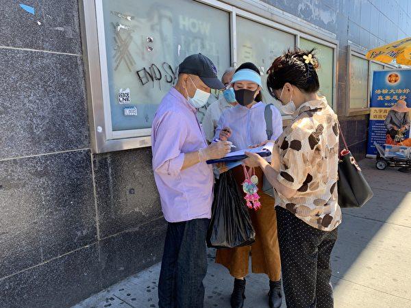 圖為一名亞裔在「拒絕中共」(Reject the CCP)的倡議書上簽字。(林丹/大紀元)