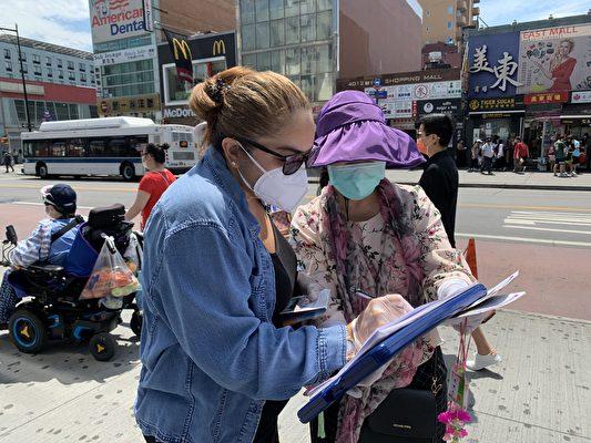 6月25日,紐約民眾在「終結共產黨」的徵簽表上簽名。(大紀元)