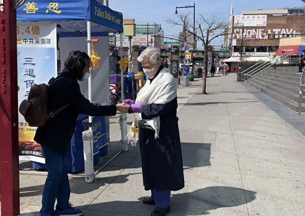 在紐約疫情最高峰的4月初,法拉盛街頭的法輪功真相點照常開放,圖為民眾接過「法輪大法好」小蓮花和護身符。(林丹/大紀元)