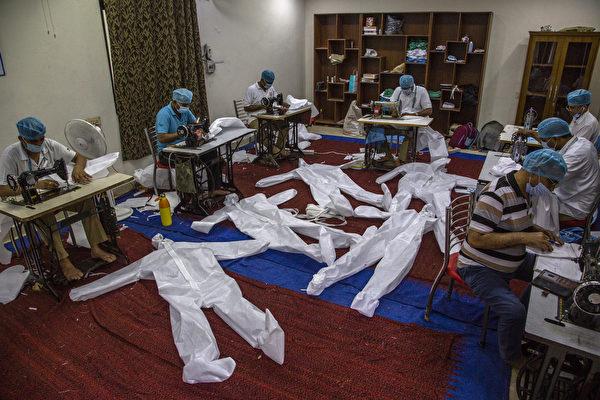 來自中央後備警察部隊的印度準軍事士兵在其營地生產個人防護設備(PPE)防護服。(Yawar Nazir/Getty Images)