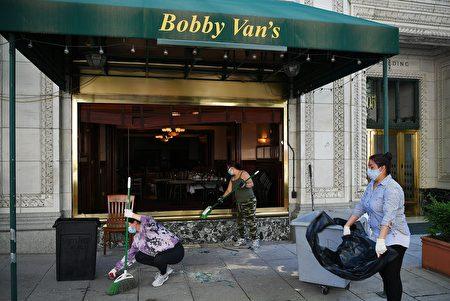 6月1日,在白宮附近一家被破壞的餐廳門外,工人們正在清掃玻璃殘渣。(MANDEL NGAN/AFP via Getty Images)