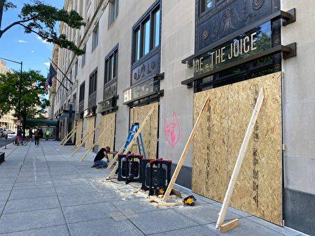 6月1日,法新社辦公室所在的大樓,在被損毀的玻璃門處擋上了木板加固。(DANIEL SLIM/AFP via Getty Images)