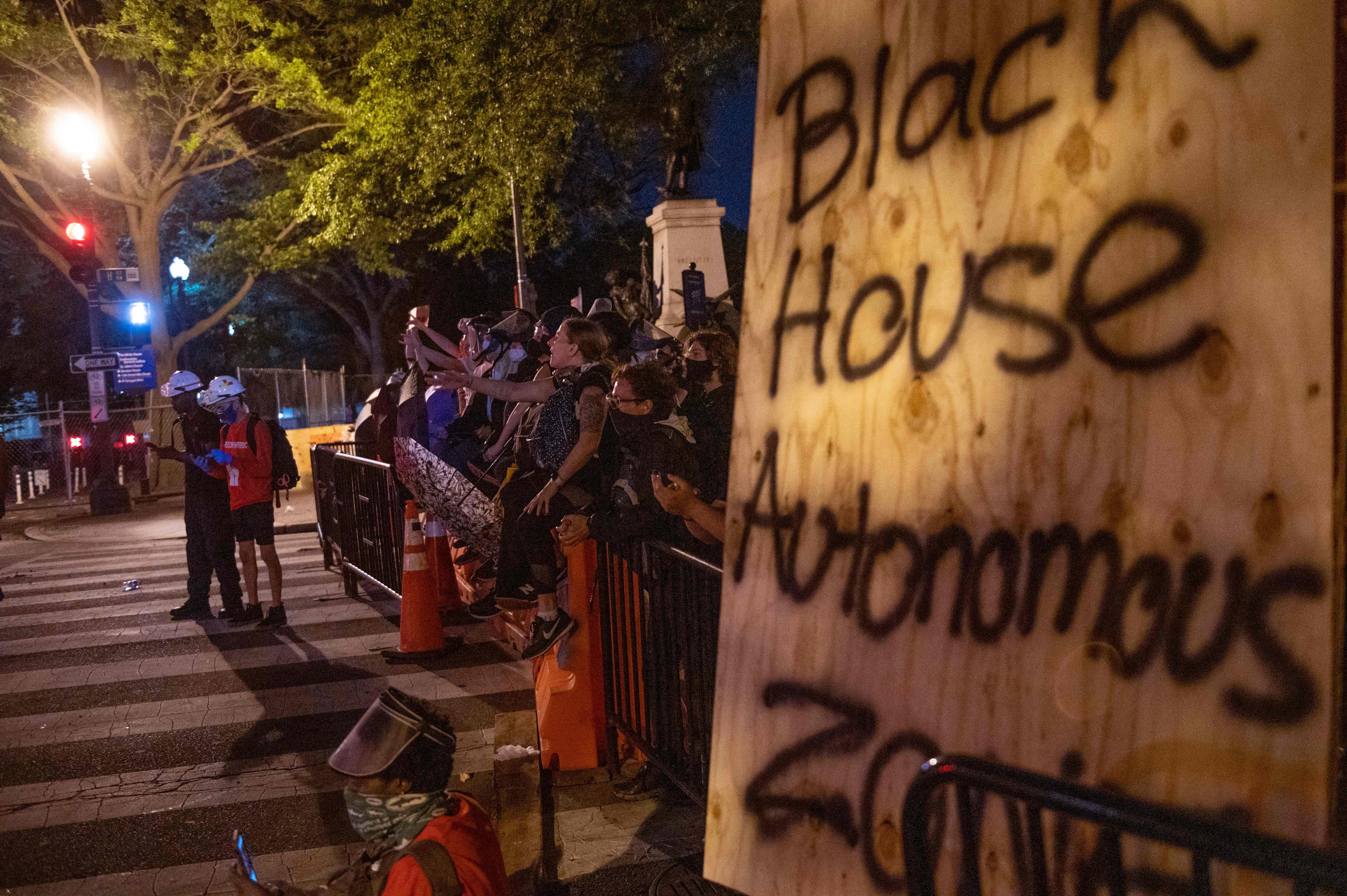 非裔弗洛伊德之死引發持續騷亂。2020年6月22日,抗議者在華盛頓特區白宮附近的拉斐特公園前豎起「黑宮自治區」路障,向警察起哄。(ROBERTO SCHMIDT/ AFP)