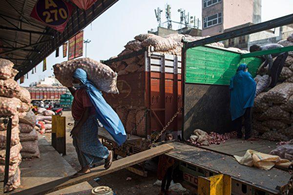 2020年6月26日,印度的阿扎德普爾(Azadpur)批發蔬菜市場,工人戴口罩搬運洋蔥袋。(XAVIER GALIANA/AFP via Getty Images)