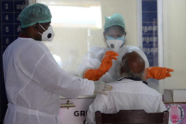 2020年6月26日,印度清奈(Chennai),醫療技術人員對一名老人採檢中共病毒樣本。(ARUN SANKAR/AFP via Getty Images)