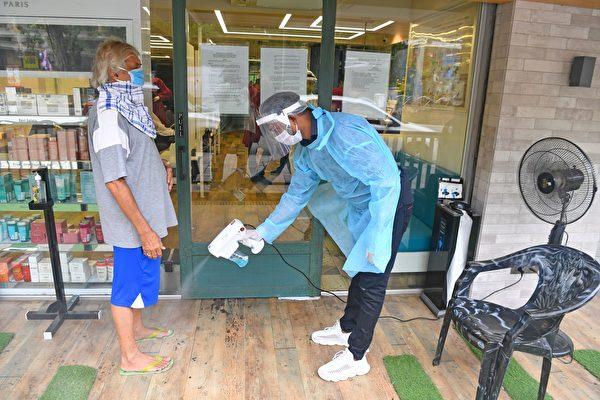 2020年6月28日,印度孟買,美髮沙龍的工作人員在入口處幫客戶消毒。(INDRANIL MUKHERJEE/AFP via Getty Images)