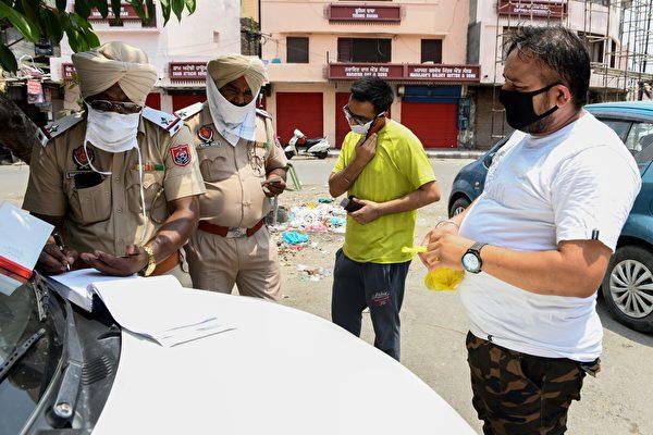 2020年6月28日,印度阿姆利則(Amritsar),警察對交通違規者開罰單,他們都戴著口罩或面罩。(NARINDER NANU/AFP via Getty Images)