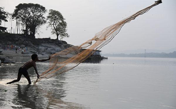 布拉馬普特拉河(Brahmaputra River,在中國境內稱雅魯藏布江)是印度人的重要命脈。圖為2018年2月17日,一名印度漁民在高哈蒂(Guwahati)河段投擲漁網捕魚。(BIJU BORO/AFP)