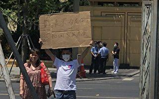 5月10日,四川维权人士谢俊彪在四川省两会期间举牌。(受访人提供)