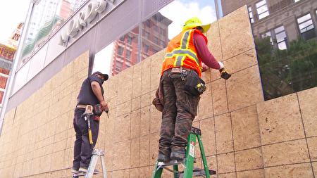 紐約市一些商家怕打砸搶的暴力示威者破壞店舖紛紛用木板釘上門。(奧利弗/大紀元)