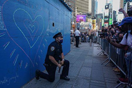 圖為紐約警察在時代廣場向抗議者單膝下跪,以化解他們的衝動。