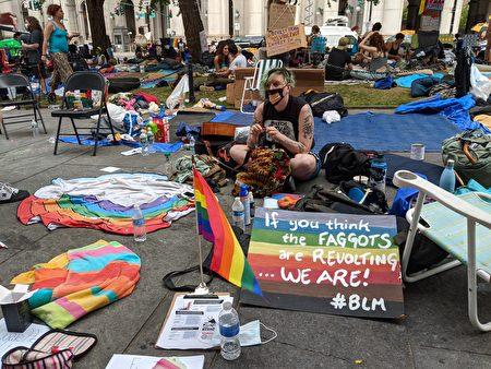支持BLM的抗議示威者席地而坐。