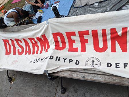 紐約市美國民主社會主義團體(NYC-DSA)製作橫幅,要求「削減警局預算」(Defund Police)。