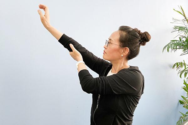五十肩复健动作一:将患侧的手臂举起到极限,然后用另外一手辅助将肩膀往上推,慢慢拉开肩关节沾黏。(大纪元)