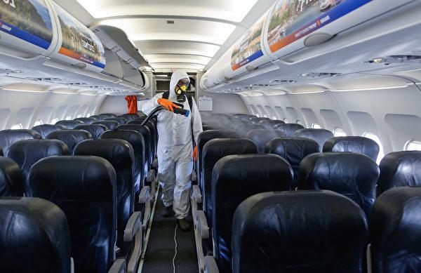 對飛機消毒。(Photo by GIL COHEN-MAGEN / AFP)