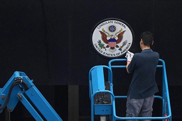 2020年7月25日,一名工人拆下美國駐成都領事館的標誌牌。(Noel Celis/AFP)