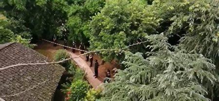 7月3日重慶市九龍坡區巴福鎮發生官員帶隊封村強拆公民房屋事件,房屋外面被人牆圍住。(影片截圖)