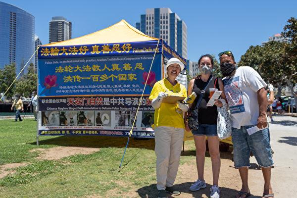 遊客聽完真相後與法輪功學員合照 。(MinghuiWang/大紀元)