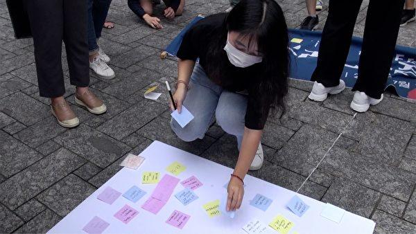 參加記者見面會的市民製作列儂牆,支持香港市民為自由抗爭。(新唐人截圖)